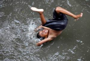 A boy plays on a flooded street during a monsoon rain in Kolkata